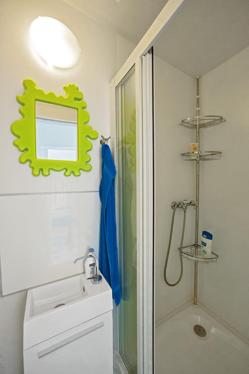 Kúpeľňa s toaletou je malá, no plne funkčná. Vaňu v stiesnenejších podmienkach nahradil sprchovací kút. Použitá biela farba priestor opticky zväčšuje, milým akcentom je zrkadlo so sviežo zeleným rámom.