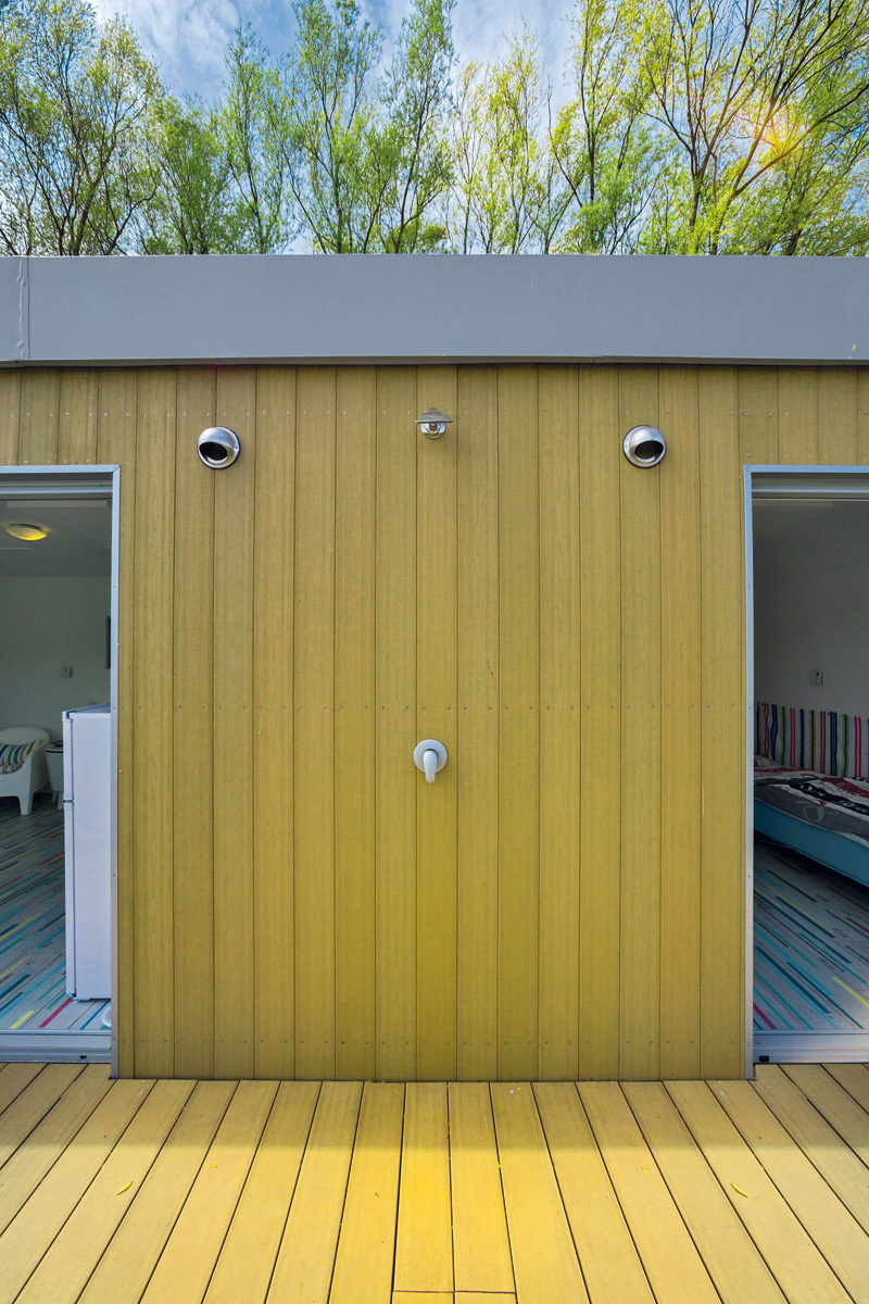 Na fasáde plávajúcej chaty sa nachádza exteriérová sprcha, ktorá slúži na opláchnutie po kúpaní sa v rieke alebo na osvieženie počas horúcich dní.