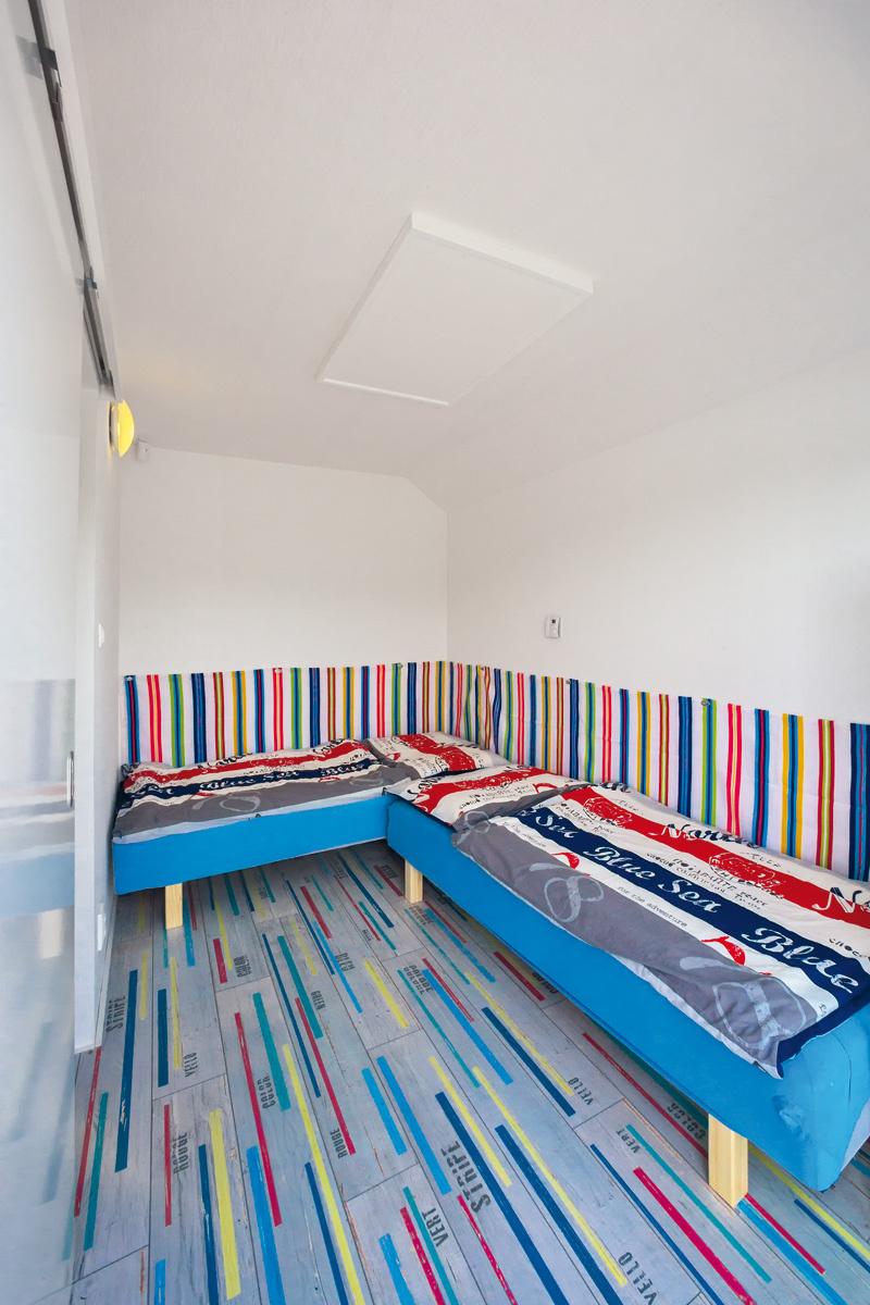 Spálne sú v plávajúcej chate dve – jedna slúži rodičom, druhá deťom. Na oživenie aj pohodlné opretie je v tej detskej za posteľami umiestnený pruhovaný látkový sokel v živých farbách, ktorý ladí s podlahou aj aktuálnou posteľnou bielizňou.