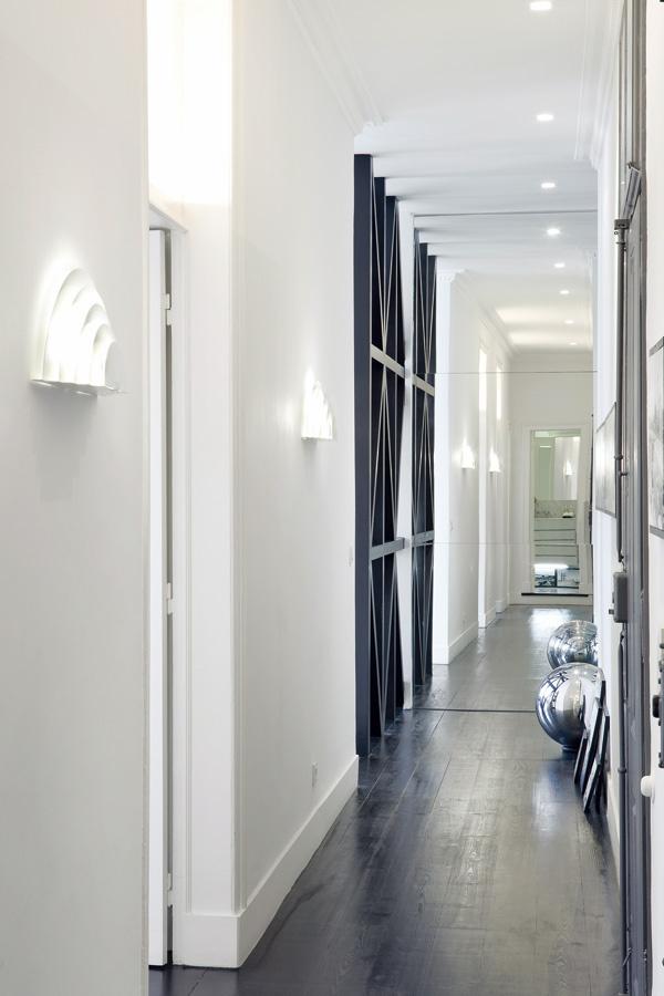 Do bytu sa vstupuje v polovici dlhej chodby, ktorá vedie naprieč celou dispozíciou. Na konci pri obývačke sa priestor chodby opticky otvára vďaka veľkým zrkadlám na dvoch susediacich stenách. (Pohľad smerom k obývačke.)