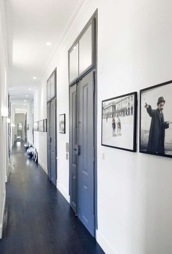 Základnú čierno-bielu farebnú kombináciu podlahy a stien, ktorá je typická pre celý byt, doplnili v chodbe čiernobiele archívne fotografie.