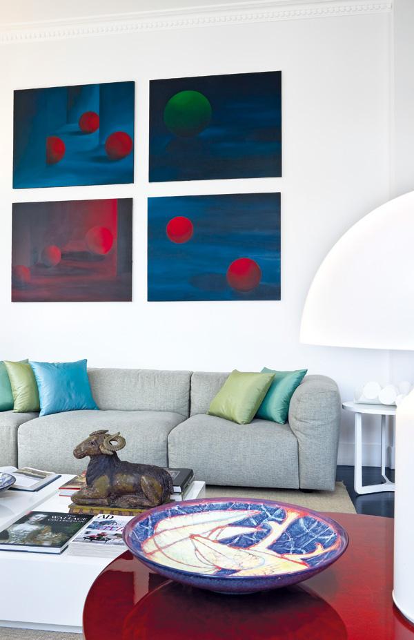 Obývačkovú časť dennej miestnosti charakterizuje svetlosivá pohovka od dizajnérskej značky Minotti, umiestnená pri stene proti oknám, ktorá vytvára harmonickú farebnú kombináciu s hodvábnymi vankúšmi v odtieňoch morskej vody. So svetlým moderným zariadením kontrastujú tmavé kusy historického nábytku a štvorica obrazov s odkazom na sýtočervený secesný stolík.