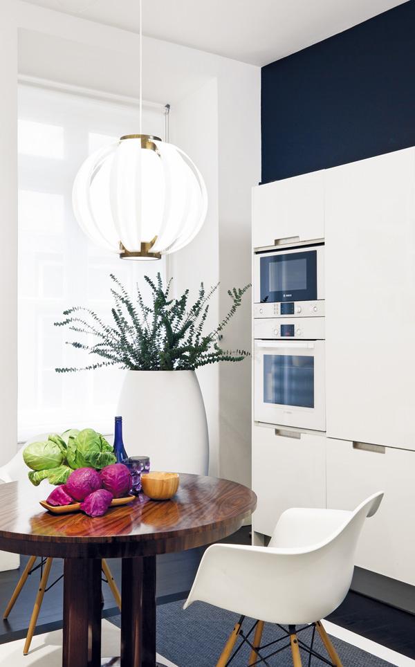 Dekoratívny stôl z palisandrového dreva z obdobia secesie dopĺňajú rovnako ako v jedálni biele eamesovské stoličky. Štýlovo pestrú kompozíciu dotvára bronzová lampa zavesená nad stolom a obrovská akrylátová váza značky Giandia Blasco pri okne.