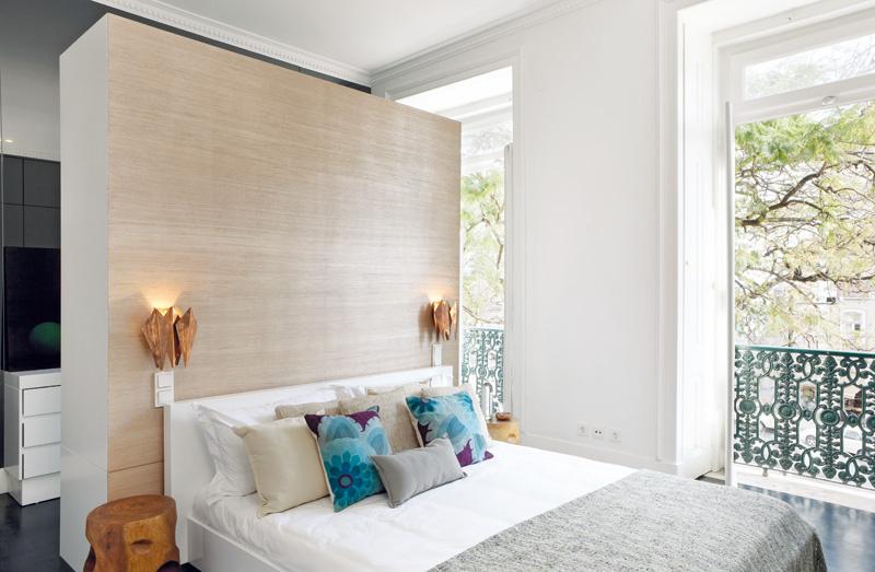 V hlavnej spálni má konštrukcia za posteľou, vyrobená na zákazku, hneď niekoľko funkcií – z jednej strany pôsobí ako čelo postele, z druhej slúži ako odkladací priestor. Zároveň vyčleňuje zo spálne akýsi šatník a miesto na prezliekanie pri kúpeľni, ktoré sa tu nedali oddeliť stavebne, priečkou siahajúcou od steny až po strop.
