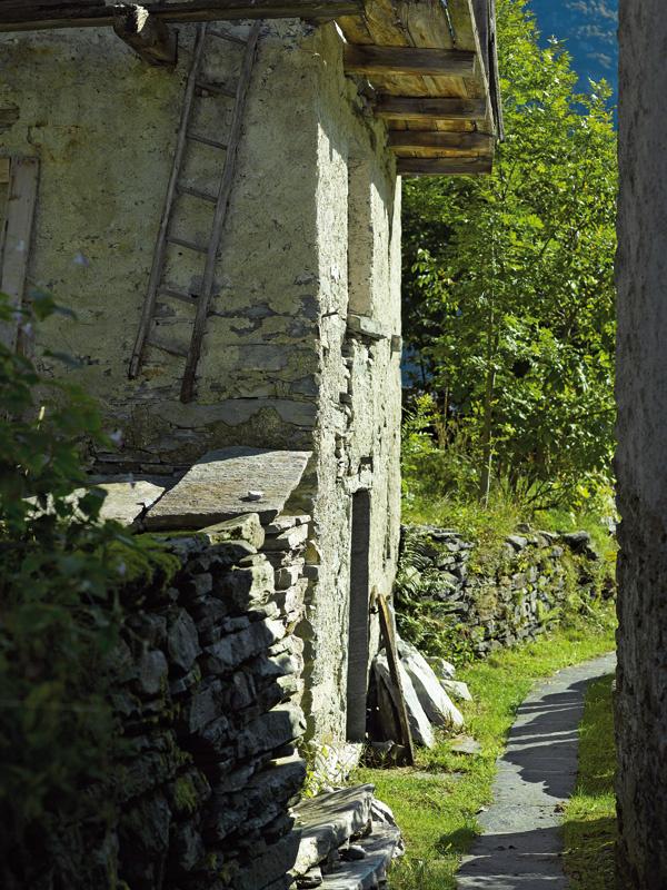 Úzka cestička lemovaná kamennými múrikmi vedie pomedzi staré poľnohospodárske budovy.