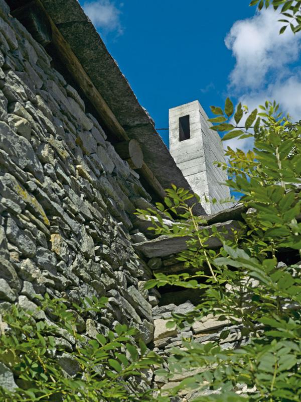 Betónový komín a sklenené dvere do záhrady sú jedinými zvonka viditeľnými dôkazmi nového života v dvestoročnej budove.