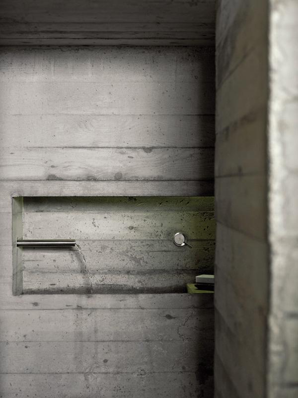 Výklenok za kozubom poskytol priestor na minimalistickú kúpeľňu – na umývadlo vytvorené zárezom v betónovej stene a toaletu.