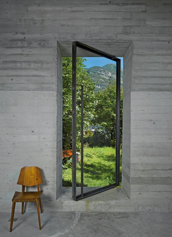 Introvertná budova má iba jedny nové dvere – sklenené v oceľovom ráme –, ktoré zároveň poskytujú výhľad na panorámu údolia. (stolička: Inch Furniture)