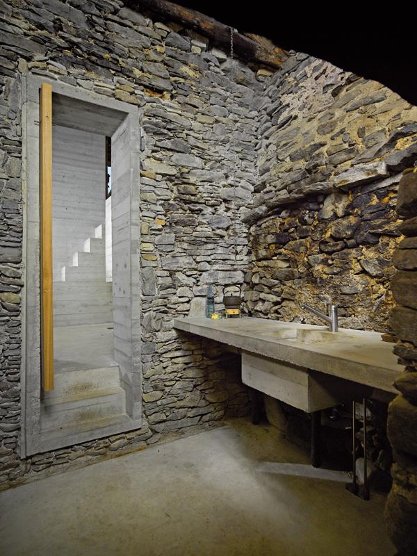 Kuchyňa v prístavbe je zredukovaná na nevyhnutné minimum. Pracovná doska aj drez sú vytvarované z betónu.