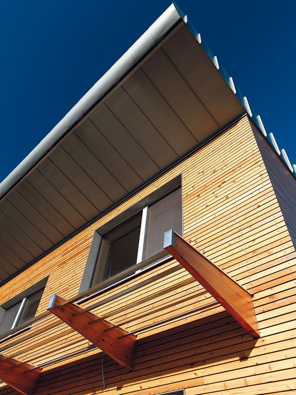 Vlete, keď je slnko vyššie, tieni južné okná na poschodí presah pultovej strechy, na prízemí zase lamelový slnolam. Čoskoro pribudne asymetrická tieniaca textília, ktorá zatieni okná obývačky aj južnú terasu – tá je bez vhodného tienenia vlete vpodstate nepoužiteľná.
