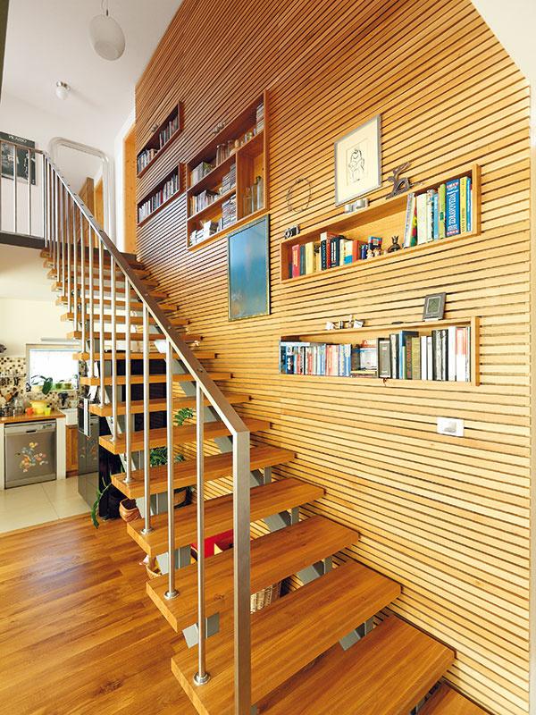 Jemný raster dreveného obkladu vinteriéri je odkazom na exteriér. Masívne drevo tu však nie je len zestetických dôvodov. Spolu snepálenými tehlami má za úlohu zlepšiť akumuláciu aabsorpciu vlhkosti vdrevostavbe. Aj preto je povrch dreva upravený len olejom. Nepálené tehly sú zabudované za dreveným obkladom steny vedľa schodiska aj vpodlahách.