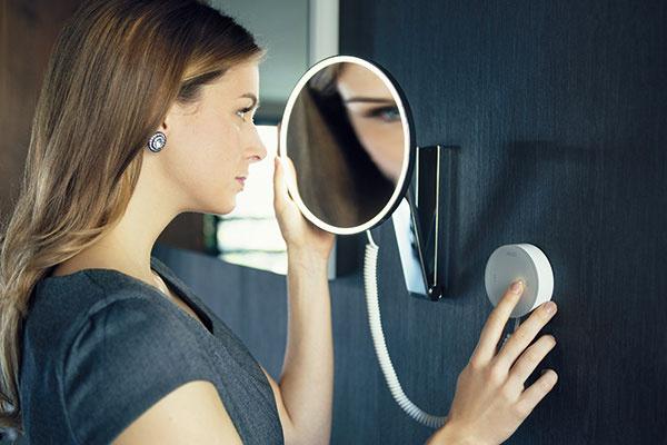 Dôležitá drobnosť – zväčšovacie kozmetické zrkadlo. Toto je na pohyblivom ramene, takže si viete šikovne nastaviť ideálnu polohu, amá vlastné LED osvetlenie, ktoré neoslňuje, jeho farbu môžete plynulo meniť. Budete tak presne vedieť, ako bude líčenie vyzerať cez deň pri jasnom bielom svetle alebo večer pri teplejšom alichotivejšom umelom osvetlení. (Zrkadlo iLook_move, Keuco)