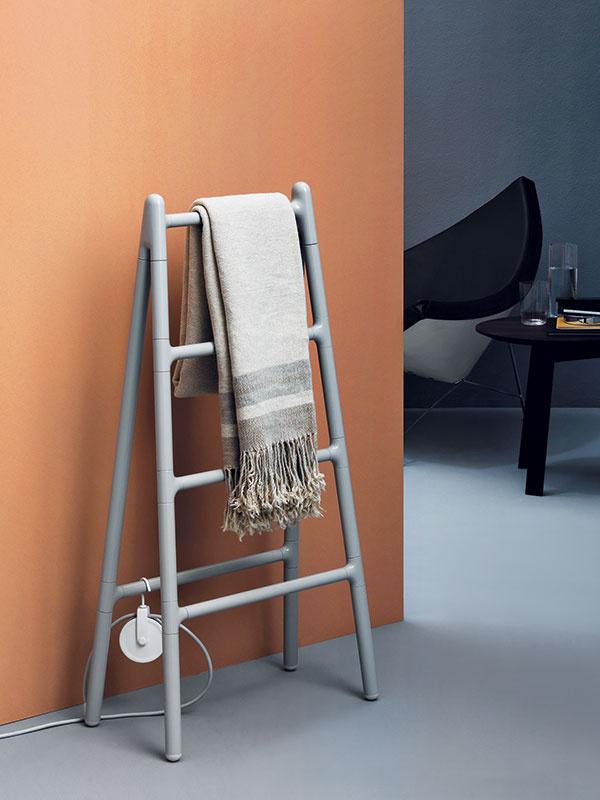 """Tento """"kúpeľňový rebrík"""" je naozaj hoden svojho mena. Mobilný hliníkový radiátor – elektrický sušiak na uteráky Scaletta – je kdispozícii v dvoch verziách – kstene alebo do priestoru. Je vybavený praktickou kladkou na navíjanie elektrického kábla amožno knemu pridať háčiky na zavesenie uterákov, kverzii do priestoru aj praktickú poličku zCorianu. (Predáva AQUA TRADE.)"""