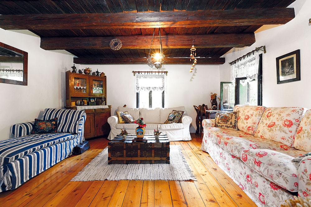 Zariadenie obývačky je kombináciou storočného dreveného nábytku asúčasných sedačiek.