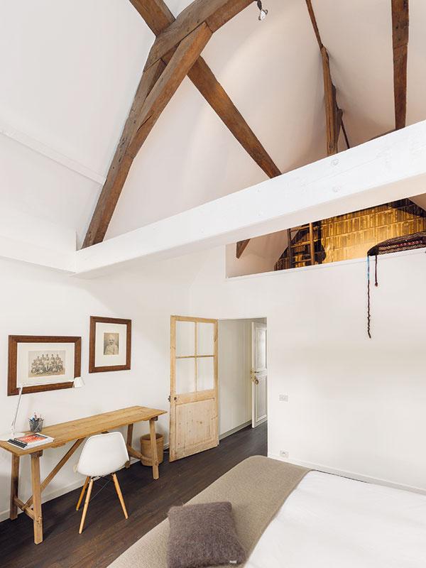 Aj vhosťovskej izbe vpodkroví dotvára čistý bielo-drevený základ interiéru niekoľko kúskov nábytku so zaujímavým dizajnom.