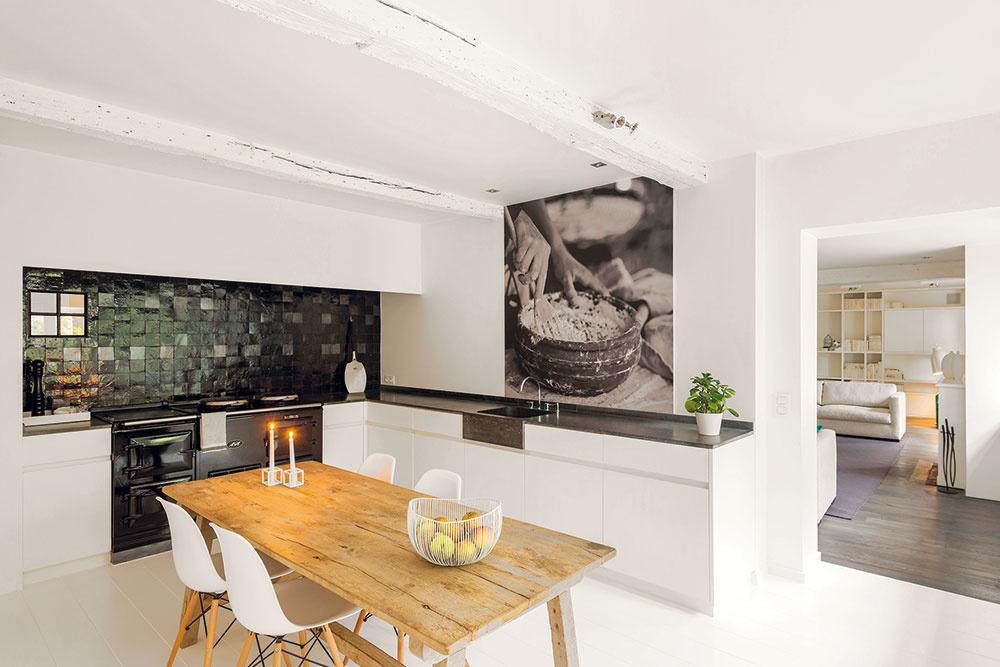 Kuchyňa je vpriamom kontakte sobývačkou. Spája ich nielen priestor akontakt so záhradou, ale aj biele steny ajednoduché vybavenie. Iba pôvodnú podlahu zdrevených dosiek vystriedala vkuchyni nová biela dlažba.