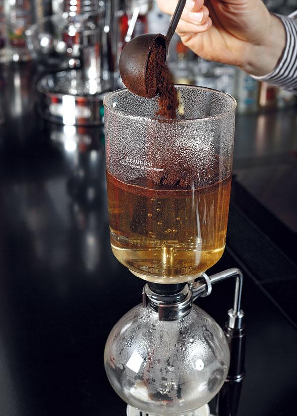 Do vody pridajte kávu, druhou stranou odmerky to poriadne premiešajte azakryte. Plameň by mal byť dostatočný na to, aby káva nezačala hneď pretekať do spodnej nádoby.