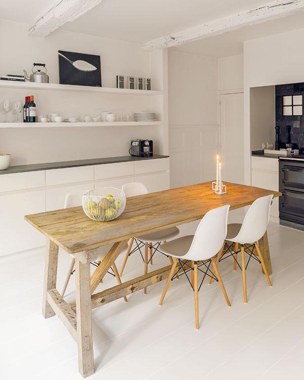 Vkuchyni vytvárajú elegantný kontrast sbielymi stenami ajednoduchou bielou linkou lesklé čierne plochy obkladačiek, pracovných dosiek aspotrebičov sretro dizajnom.