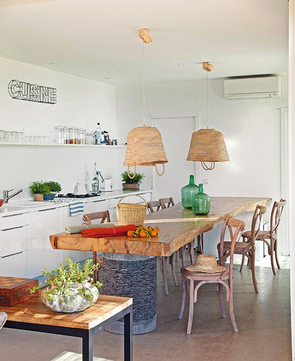 Na obývačku priamo nadväzuje otvorená moderná kuchyňa. Pôsobivý kontrast kjednoduchej bielej linke vytvára originálny jedálenský stôl zmasívneho dreva, ktorý navrhla interiérová dizajnérka Patricia Ramos. Zmestí sa zaň až dvanásť ľudí. (stôl alampy Patricia Ramos, stoličky Maison du Monde)