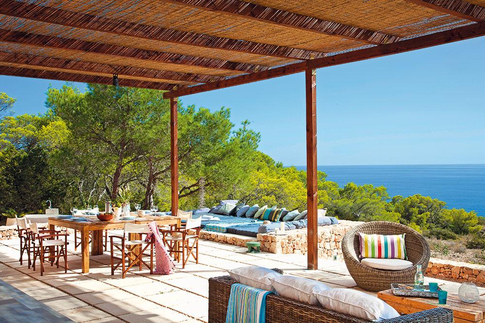 Najdôležitejšie anajobľúbenejšie miesto na stolovanie je vonku na terase. Svýhľadom na more, vtieni jednoduchej drevenej markízy krytej bambusovými rohožami. (stoly apohovky Maison du Monde, stoličky Casa Paya, vankúše auteráky Catalina House)