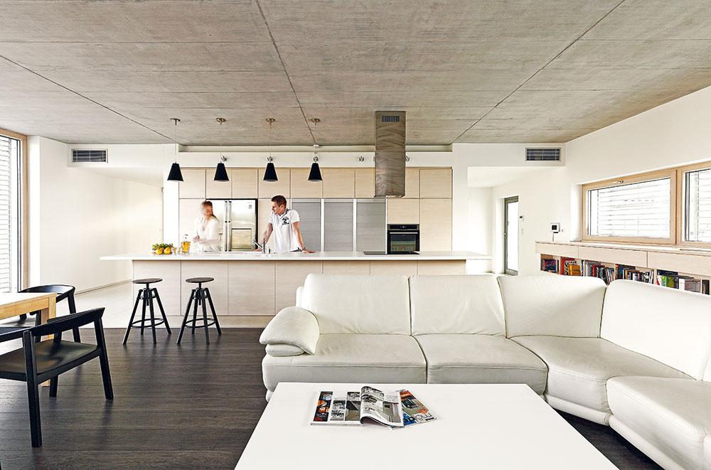 Kuchyňa pozostávajúca zo zabudovaných vysokých skríň aostrovnej časti je umiestnená presne na osi priestoru. Majitelia tak majú pri varení kontrolu nad tým, čo sa deje vátriu, vovstupnej časti pozemku aj vobývacej izbe.