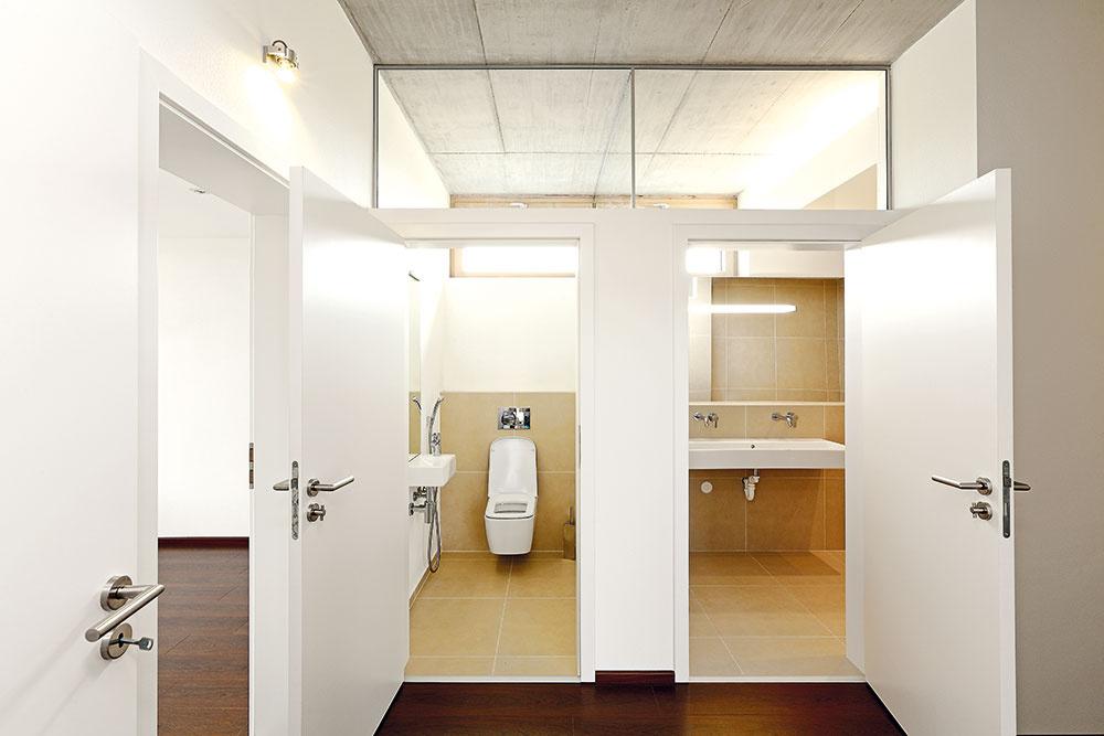 Svetlíky nad dverami kúpeľní atoaliet slúžia na presvetlenie dlhej tmavej chodby denným svetlom azároveň tlmia jej tunelový efekt.