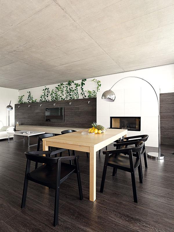 Jedálenský stôl pre šesť ľudí osvetľuje stojacia lampa, ktorá nevyžaduje zásah do betónového stropu.