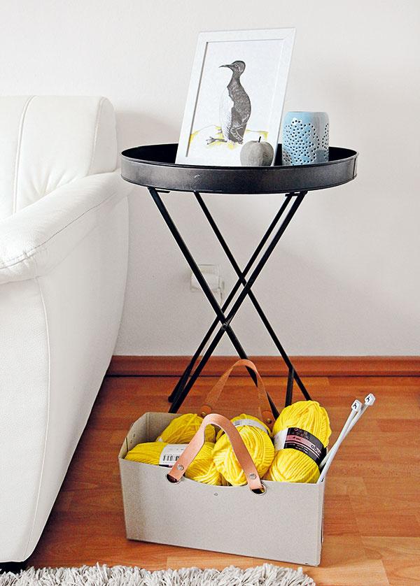 """Osadenstvo vedľa sedačky vobývačke sa zčasu na čas zmení – od stolíka až po dekorácie. Keď je bielej priveľa, stolík zIKEY nahradí čierny plechový od Broste anaopak. Akilo citrónov """"čendžne"""" lepenkový kôš od značky Kazeta spletacou priadzou."""