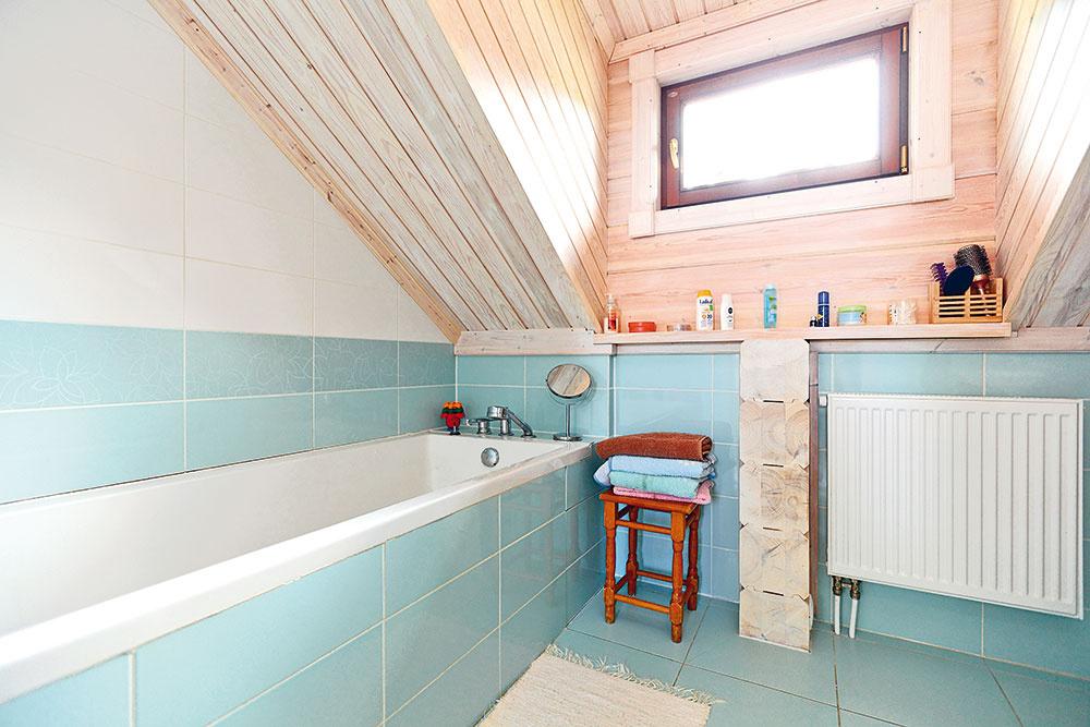 Vkúpeľni na poschodí vytvárajú príjemnú atmosféru drevené steny vpokojnej farebnej kombinácii spastelovomodrým abielym obkladom.