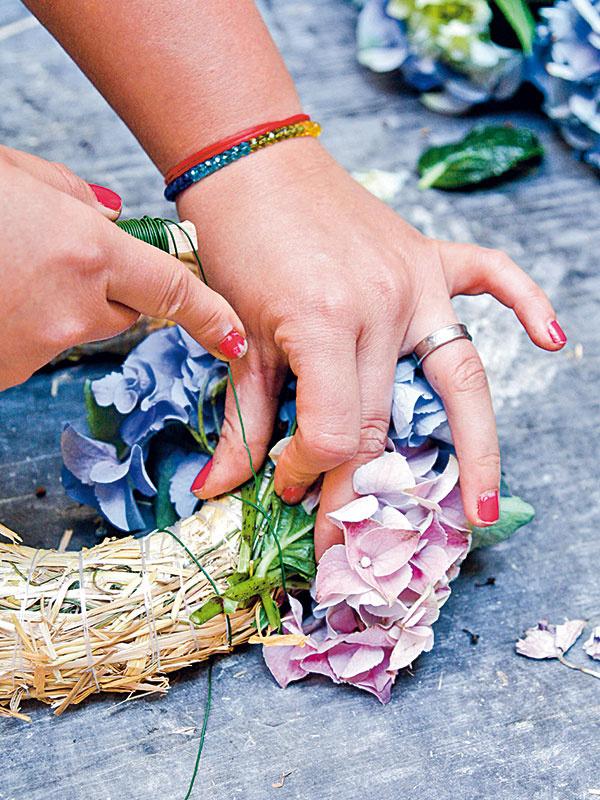 3 Nastrihané hortenzie prikladajte ľavou rukou na telo venca, kým nepokryjú celý jeho obvod. Pomocou pravej ruky jednotlivé hortenzie postupne oviňte drôtom tak, aby ste upevnili spodnú časť stonky.