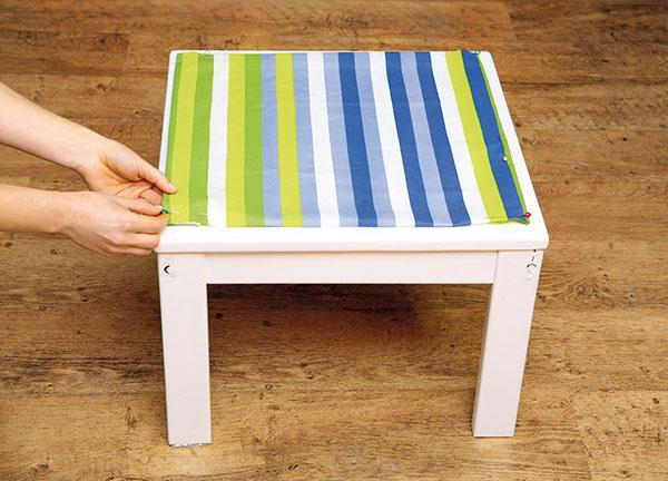 Zlátky vystrihnite štvorec srozmermi 50 × 50 cm (podľa stolčeka) ajeho okraje zahnite dovnútra (asi 2 cm).
