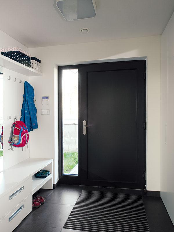 Vstupné dvere majú rovnakú farbu ako hliníkové rámy okien. Ich súčasťou je aj bočný svetlík, ktorý zaisťuje denné svetlo vpriestore zádveria.