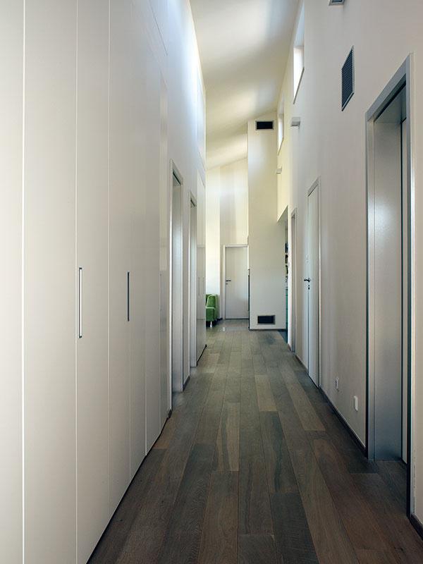 Skriňové mimikry. Na to, aby architektka vytvorila vdome čo najviac odkladacích priestorov, využila aj dlhú chodbu – nenápadne ju lemujú biele dvere vstavaných skríň na celú výšku priestoru, vktorých sa nájde miesto napríklad aj na športové vybavenie. (Pohľad smerom kobývačke.)