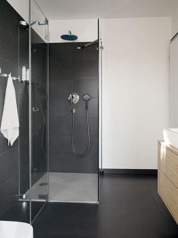 Spojenie rodičovskej spálne skúpeľňou (takzvaná kúpeľňa en suite) patrí kpríjemným moderným riešeniam, ktoré sa už aj unás tešia čoraz väčšej obľube. Pôsobivú kombináciu veľkoformátového obkladu vmatnej antracitovej farbe, lesklej bielej keramiky asvetlého dreva tu sgráciou dopĺňajú ďalšie ušľachtilé materiály – sklo achróm.