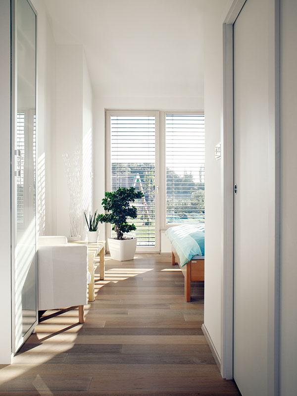 Na západnom konci domu uzatvára rad obytných miestností spálňa rodičov – ako inak, sveľkými sklenenými dverami, ktoré vedú na terasu. Záľuba domácich vjednoduchých riešeniach aprírodných materiáloch je tu zrejmá na prvý pohľad.