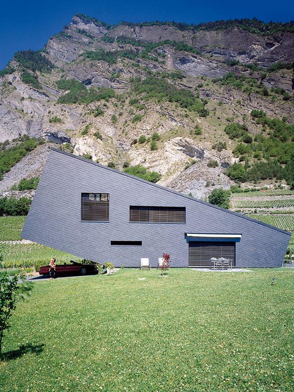 Prístrešok na auto môže vzniknúť aj šikovným využitím architektúry domu či daností pozemku – napríklad svahu. (Dom – naklonený hranol vo švajčiarskom kantóne Vallis