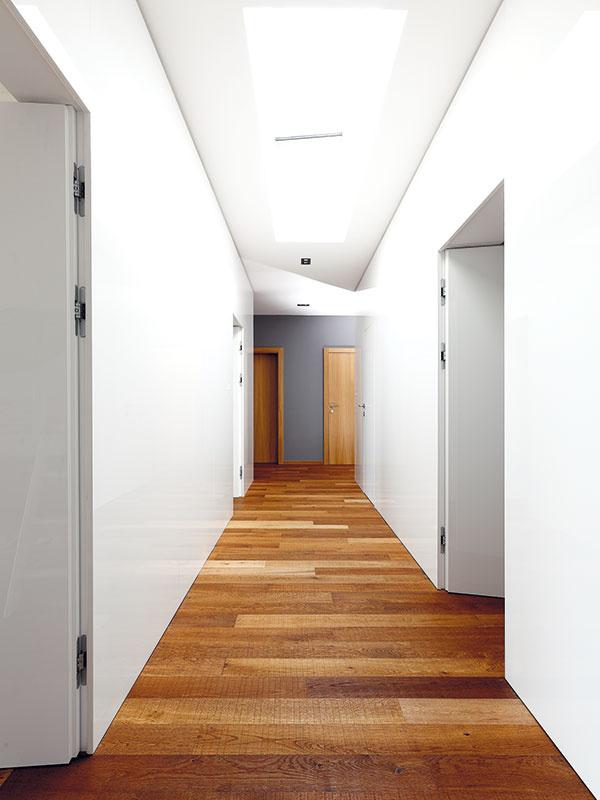 """Vchodbe vnočnej časti domu je šestoro dverí, čo bola pre architekta zaujímavá výzva: """"Nechcel som, aby to vyzeralo ako vhoteli: dvere, zárubňa, kúsok omietky, zárubňa, dvere... Navrhli sme preto veľmi čisté riešenie, kde nevidno zárubne advere lícujú so stenou. Našťastie, už dlhšie spolupracujeme sfirmou, ktorá dokáže zrealizovať aj takéto náročné detaily."""""""