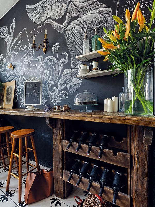 2 v1. Súčasťou masívneho na mieru vyrobeného barového stola je šikovná vinotéka, do ktorej možno odložiť napríklad aj domáce sirupy. Stoličky zo svetlejšieho dreva pekne kontrastujú so stolom aj tabuľovým náterom asú príjemným oživením.