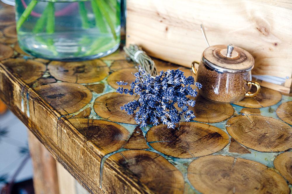 Štýlový drevený bar zaujme najmä svojou pracovnou doskou, tvorenou prierezmi drevených klátikov. Podobným spôsobom možno vyhotoviť napríklad kuchynský ostrov vo vidieckom či vintage štýle.