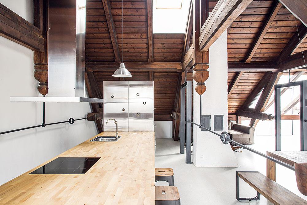Aby podkrovie plné tmavého dreva nepôsobilo ponuro, snažili sa doň architekti vniesť viac svetla apocit vzdušnosti svetlými alesklými plochami – kuchynskou linkou santikorovými dvierkami, bielymi stenami atakmer bielou podlahou.