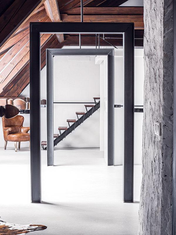 """Dvere bez stien. Nech sa páči, vstúpte – dverami bez steny. Architekti nahradili niekdajšie rektifikačné oká """"zárubňami"""" zoceľových profilov, čím sa im podarilo priestor šalamúnsky prepojiť, zobytniť, apritom nenarušiť."""