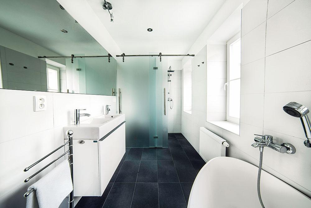 Kúpeľňa sa ako jediná vymyká zcelkového štýlu bytu – má celkom štandardné vybavenie ačistý, takmer čierno-biely obklad. Všetko sa nesie vduchu jednoduchosti arozumnej investície.