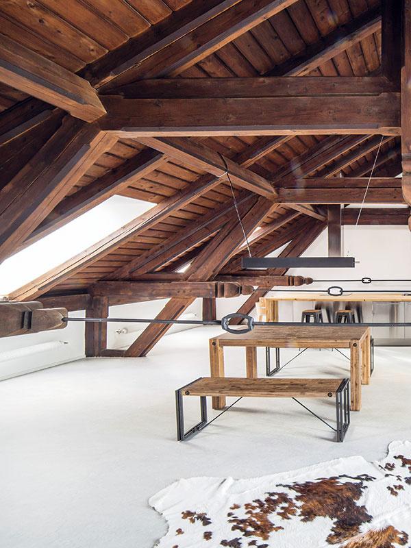 Pôvodnú podlahu (alebo skôr nerovný strop nad aulou) vyrovnali aako povrchovú vrstvu zvolili marmoleum. Vkontraste sjeho svetlou jednoliatou plochou tak vyniknú filigránske detaily tmavého krovu.
