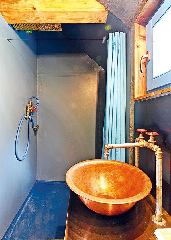Medené umývadlo je prácou majstra zNových Zámkov, ktorý vyrába umývadlá na jachty. Akeďže mal potrebné kopyto na jeho výrobu, stálo Elišku len zopár eur. Vsprche je obyčajná záhradná hadica. Musela byť modrá.