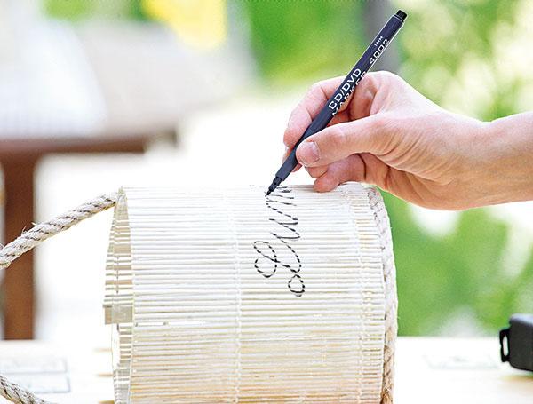 Na zhotovený svietnik sbielym povrchom napíšte fixkou nápis anásledne ho môžete ešte prestriekať lakom vspreji. Ak chcete niečo napísať aj na stranu spozatekanou farbou, môžete použiť biely odtieň.