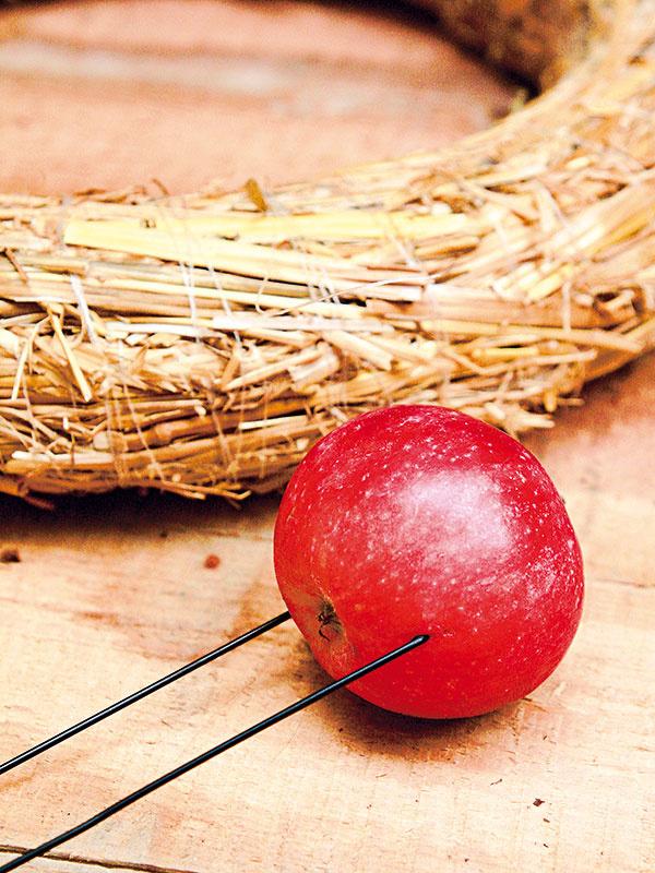 Ako prvú si vytvorte kostru venca z nadrôtovaných jabĺčok. Jednotlivé jabĺčka zhruba v ich strede prepichnite drôtom a drôt zahnite.