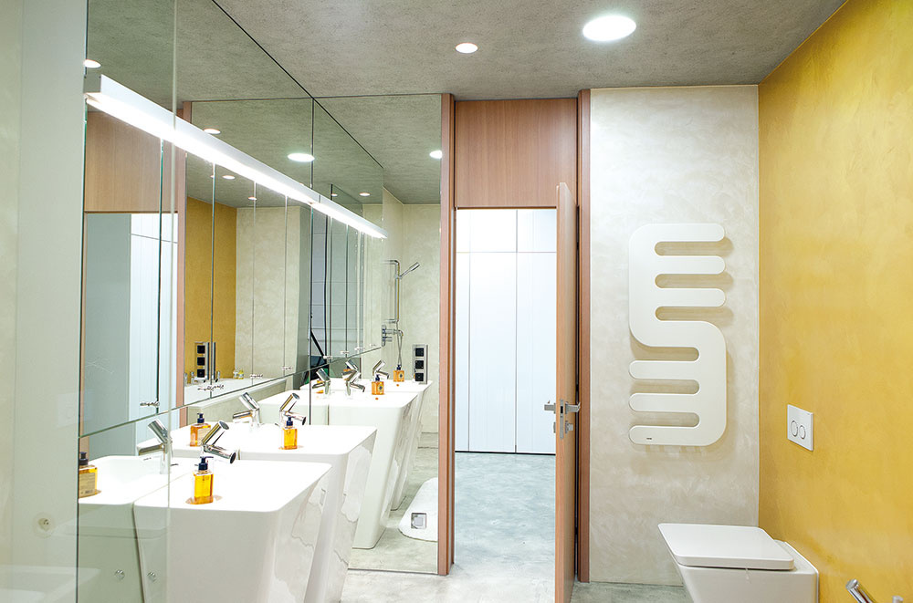 """Bez škár. Kúpeľňu pri rodičovskej spálni farebne oživuje vodoodolná stierka vteplom odtieni žltej. Aj tu ostal architekt Kotek verný priestorotvornej hre veľkých hladkých plôch, pri všetkých povrchových úpravách dodržal tiež praktickú zásadu """"bez škár""""."""