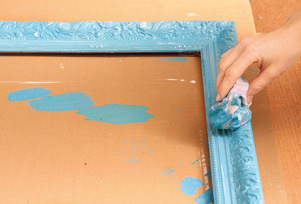 Keď farba začne schnúť (asi o10 minút), rám pretrite vlhkou handričkou – tak na miestach, kde je ornament vystúpený, zotriete modrú farbu aodkryjete biele plochy.