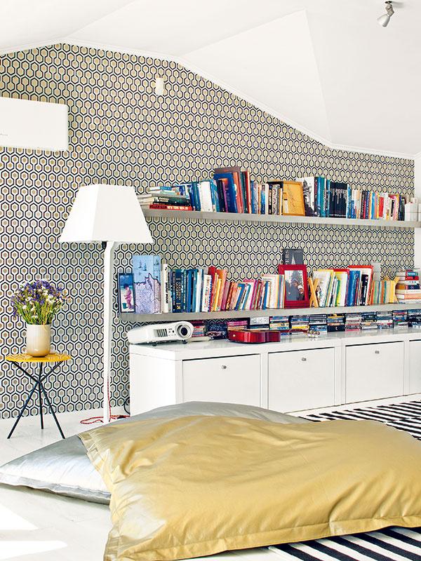 """Rozdvojená obývačka. Zpôdorysného členenia obývačky prirodzene vyplynulo jej rozdelenie na dve časti. Vrelatívne oddelenom kúte je miesto na relax spolicami plnými kníh as veľkými sedacími vakmi, či skôr """"ležacími vankúšmi""""."""