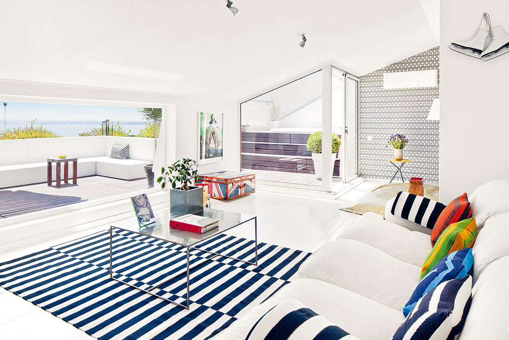 Zdanlivo nekonečný priestor. Hlavnej časti obývačky dominuje pohodlný biely gauč. Oproti nemu rozširuje priestor široké okno vedúce na terasu anekonečný modrý výhľad ponad hladinu mohutnej rieky.
